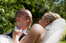 Bride being carried off by her bridegroom on their wedding day in Essex