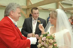 Toastmaster Richard Palmer handing bride and bridegroom a glass of champagne