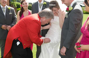 Toastmaster removing stain from bride's dress with dry cleaning kit at Stock Brook Manor Wedding